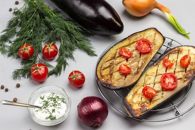 Gegrillte gebackene auberginen mit tomaten auf metallgrill dill und tomaten auf tisch sauce in glasschüssel