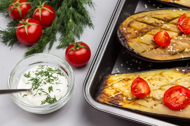 Gegrillte gebackene auberginen mit tomaten auf palette. dill und tomaten auf dem tisch. sauce in glasschüssel. grauer hintergrund. draufsicht.