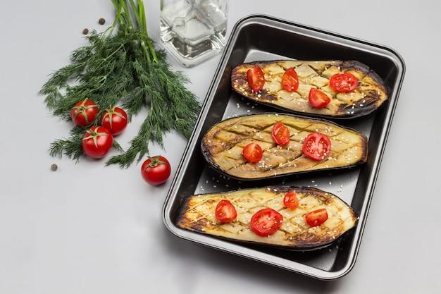 Gegrillte gebackene auberginen mit tomaten in palette dill und tomaten auf dem tisch
