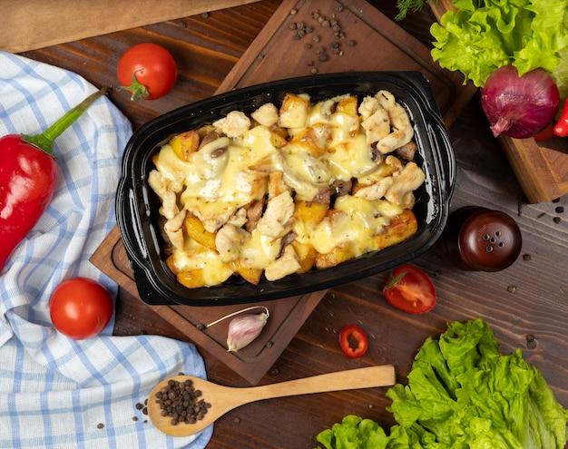 Gegrillte gebratene rindfleischstücke und kartoffelscheiben in geschmolzenem frischkäse