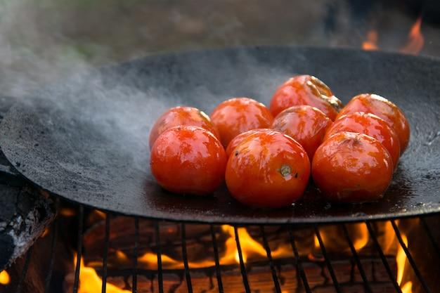 Gegrillte gebratene tomaten in einer heißen pfanne auf offenem feuer