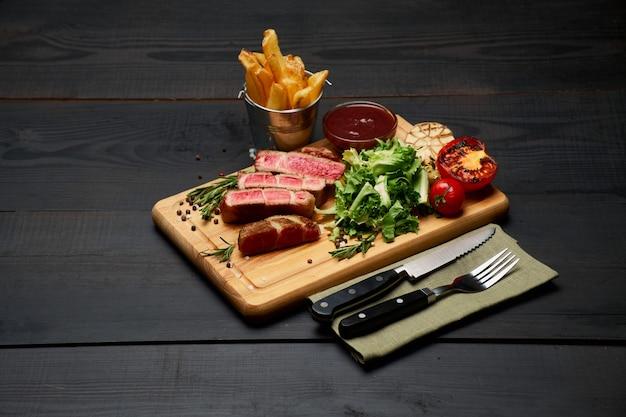 Gegrillte gegrillte roastbeefsteaks kartoffel und sauce auf holzbrett cutting