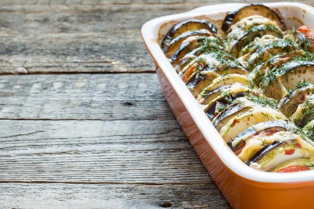 Gegrillte gemüse zucchini-auberginen-tomate eine art ratatouille auf einem rustikalen hölzernen hintergrund