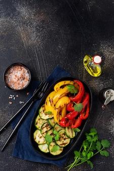 Gegrillte gemüsestücke von zucchini, rotem und gelbem pfeffer und koriander auf einem teller, salat auf einem grillrost über holzkohle. grillkonzept.