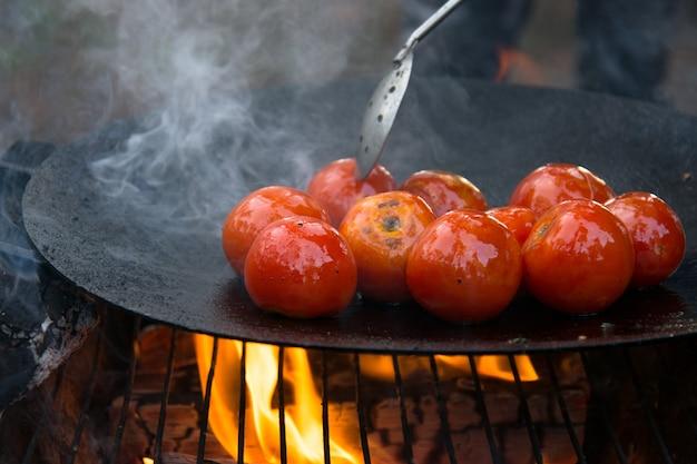 Gegrillte geröstete tomaten auf einer heißen pfanne am offenen feuer