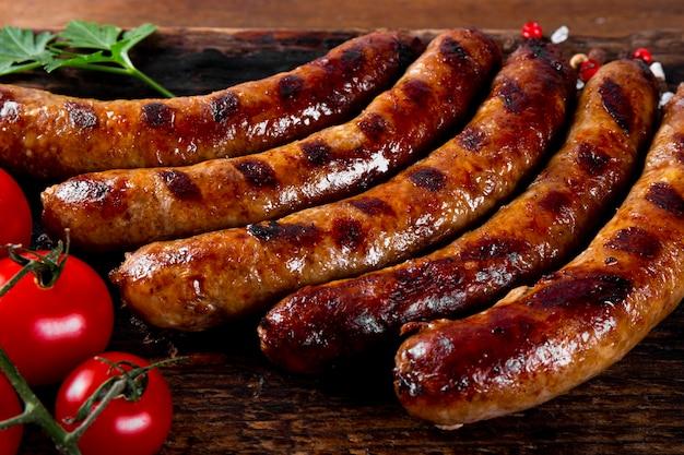 Gegrillte hackfleisch- und schweinewürste auf holzbrett hautnah.