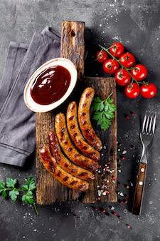 Gegrillte hackfleisch- und schweinewürste mit barbecue-sauce auf vertikalem foto der draufsicht des hölzernen schneidebretts.