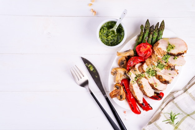 Gegrillte hähnchenbrust auf einem teller mit tomaten, spargel und champignons auf einem teller, flach legen