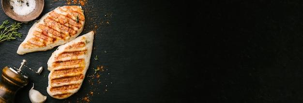 Gegrillte hähnchenbrust serviert auf schwarzem schiefer