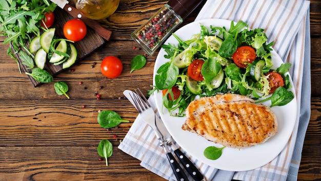 Gegrillte hähnchenbrust und frischer gemüsesalat - tomaten, gurken und salatblätter. hühnchensalat. gesundes essen. flach liegen. ansicht von oben