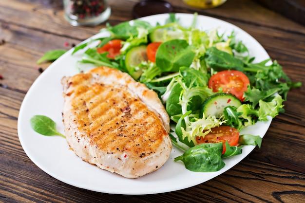Gegrillte hähnchenbrust und frischer gemüsesalat - tomaten, gurken und salatblätter. hühnchensalat. gesundes essen.