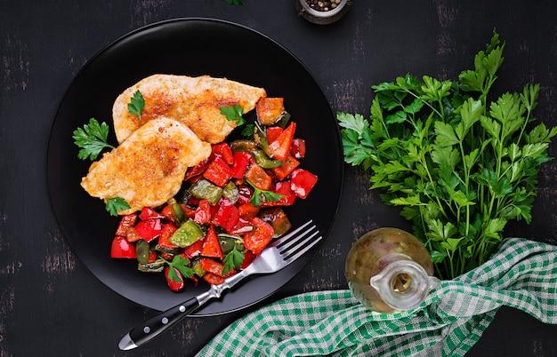 Gegrillte hähnchenfilets und paprika auf schwarzem teller