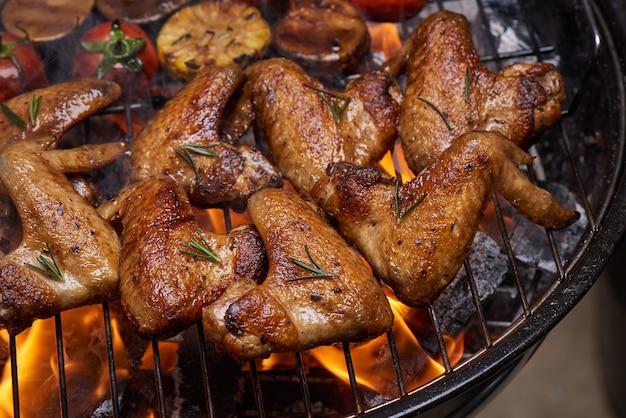 Gegrillte hähnchenflügel auf dem brennenden grill mit gegrilltem gemüse in barbecue-sauce mit pfeffersamen rosmarin, salz.