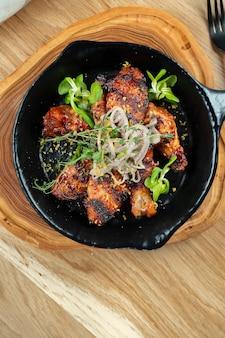 Gegrillte hähnchenflügel in honig-bier-sauce in einer dekorativen pfanne mit kräutern. nahaufnahme, selektiver fokus. holzwand. lebensmittelfoto