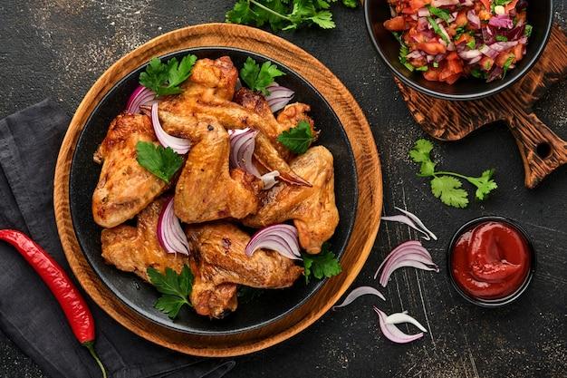 Gegrillte hähnchenflügel oder gerösteter grill mit gewürzen und tomatensalsasauce auf einem schwarzen teller