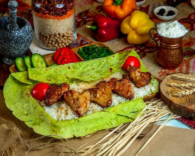 Gegrillte hähnchenflügel serviert mit reis und tomaten in fladenbrotverpackung