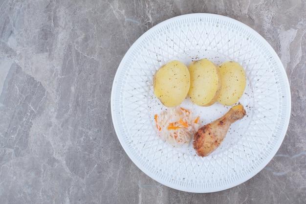 Gegrillte hähnchenkeule, kartoffel und sauerkraut auf weißem teller.