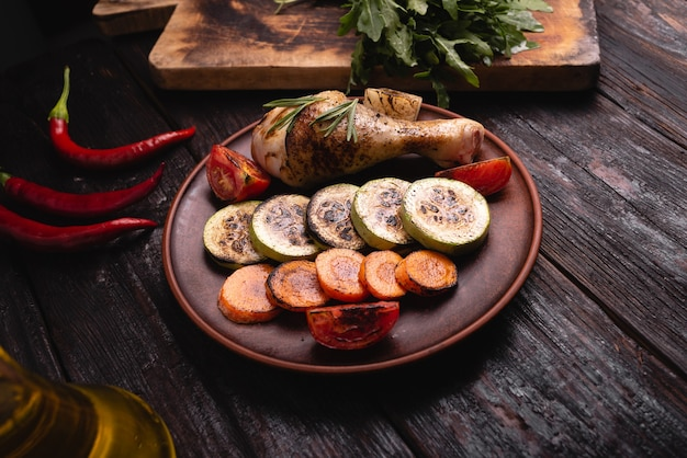 Gegrillte hähnchenkeule, leckeres saftiges fleisch mit mittlerem braten, aromatischem gemüse und glühendem chili