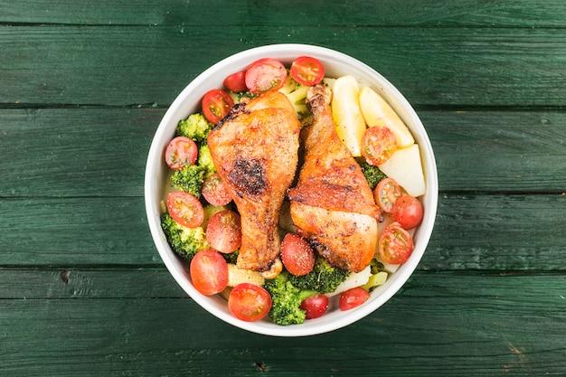 Gegrillte hähnchenkeule mit salzkartoffeln und gemüse
