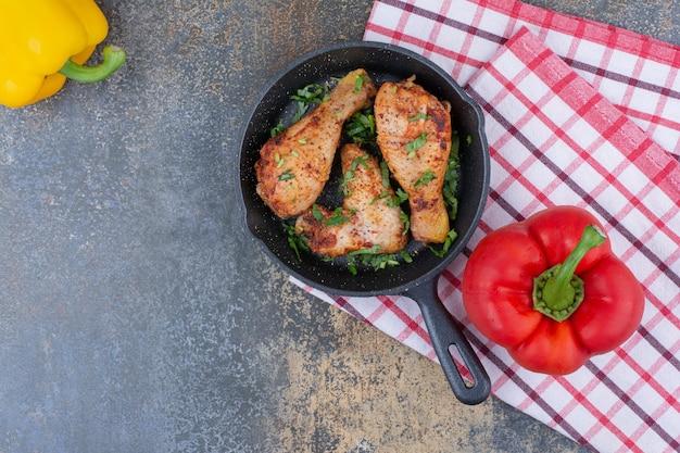 Gegrillte hähnchenkeulen auf pfanne mit paprika. foto in hoher qualität
