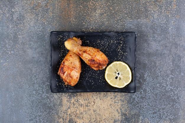 Gegrillte hähnchenkeulen auf schwarzem teller mit zitrone. foto in hoher qualität