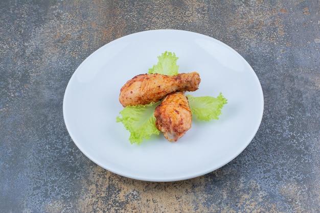 Gegrillte hähnchenkeulen auf teller mit salat. foto in hoher qualität