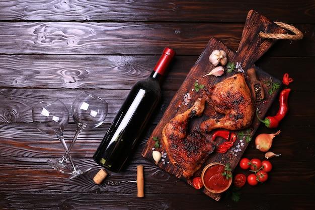 Gegrillte hähnchenkeulen mit gewürzen und gemüse, dazu eine flasche rotwein.
