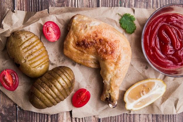 Gegrillte hähnchenschenkel mit kartoffeln; halbierte tomate; zitrone und tomatensauce auf braunem papier