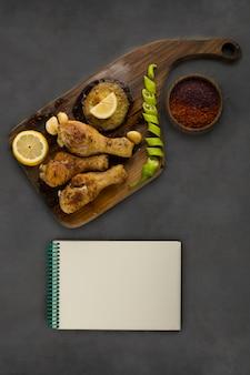 Gegrillte hähnchenschenkel serviert mit zitrone und chili, draufsicht