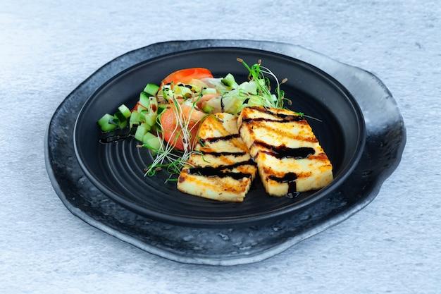 Gegrillte halloumi-käsescheiben mit gemüsesalat, tomaten und gurken