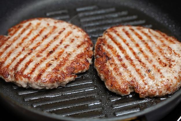 Gegrillte hamburgerkoteletts auf bratpfanne