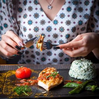 Gegrillte hühnchensteakfrau der nahaufnahme isst mit einem messer und einer gabel mit beilage, tomate, pfeffer einen dunklen holztisch horizontal