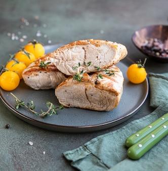 Gegrillte hühner- oder putenbrust mit kirschtomaten und thymian auf einer keramikplatte