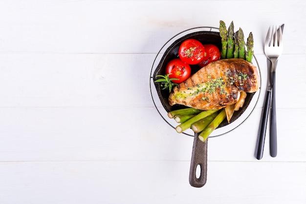 Gegrillte hühnerbrust auf einer gusseisernen pfanne mit grillgemüse auf einer holzoberfläche