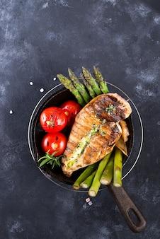 Gegrillte hühnerbrust auf einer gusseisernen pfanne mit grillgemüse auf einer steinoberfläche
