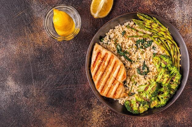 Gegrillte hühnerbrust mit braunem reis, spinat, brokkoli, spargel, konzept der diät, gesunde ernährung.