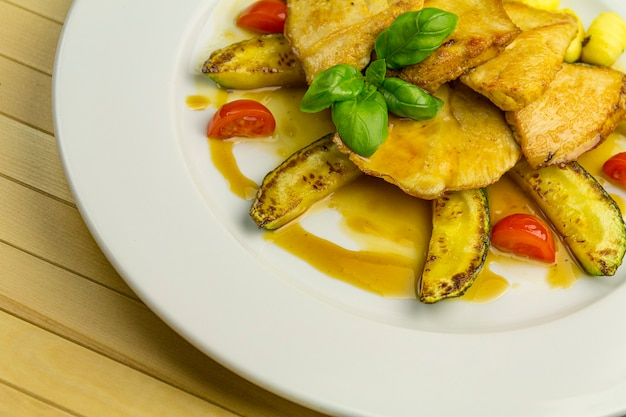 Gegrillte hühnerbrust, mit gemüse auf einem weißen teller, nahaufnahme, holztisch
