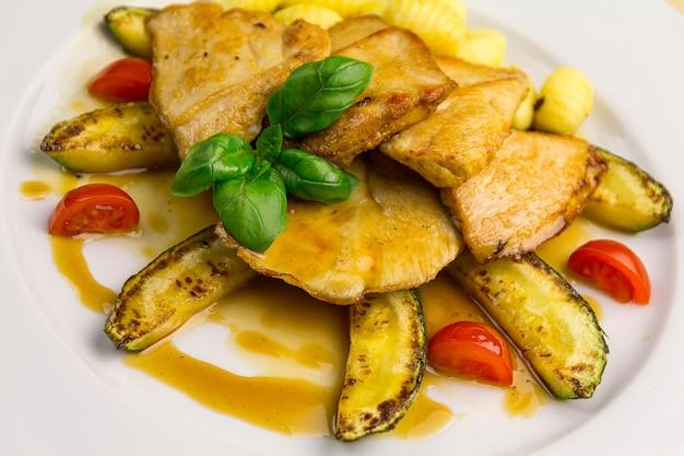 Gegrillte hühnerbrust, mit gemüse auf einem weißen teller, nahaufnahme