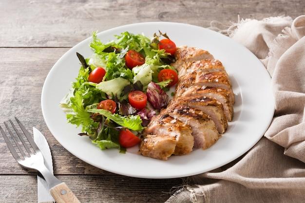 Gegrillte hühnerbrust mit gemüse auf einer platte auf holztisch