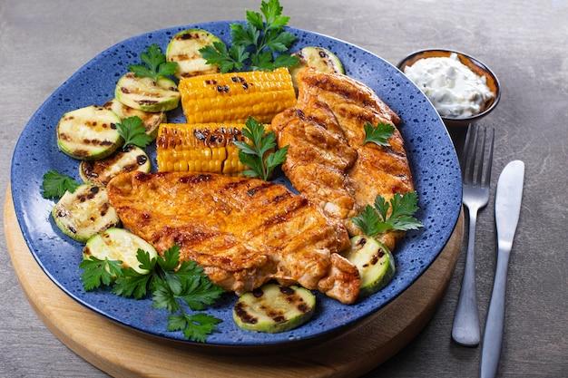 Gegrillte hühnerbrust mit mais und zucchini auf einem blauen teller hautnah. sommergericht mit gegrilltem huhn und gemüse.