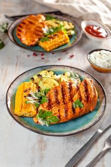 Gegrillte hühnerbrust mit mais und zucchini auf einer blauen platte-draufsicht. sommergericht mit gegrilltem huhn und gemüse.
