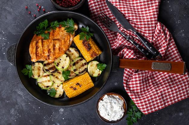 Gegrillte hühnerbrust mit mais und zucchini auf einer draufsicht der pfanne. sommergericht mit gegrilltem huhn und gemüse.