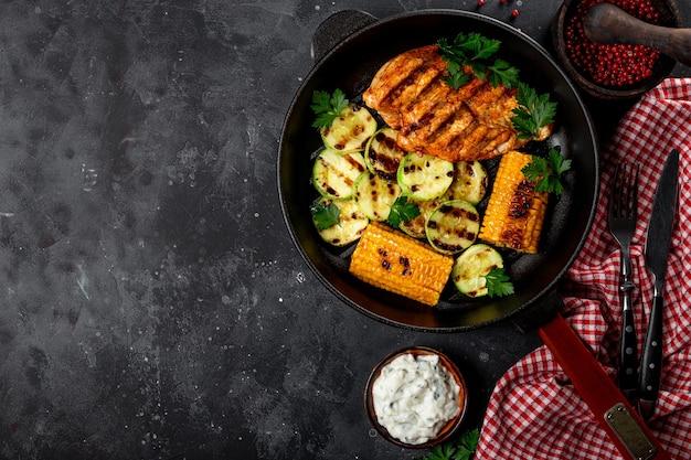 Gegrillte hühnerbrust mit mais und zucchini auf einer gegrillten pfanne draufsicht. sommergericht mit gegrilltem huhn und gemüse.