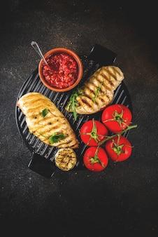 Gegrillte hühnerbrust mit tomaten und kräutern der würzigen soßen auf dunklem rostigem hintergrund