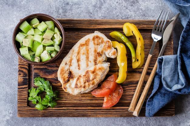 Gegrillte hühnerbrust mit tomaten- und pfeffergrill und salsa von der avocado auf holzbrett