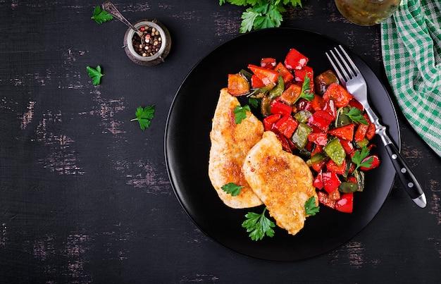 Gegrillte hühnerfilets und gemüsepaprika auf schwarzblech
