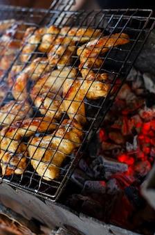 Gegrillte hühnerflügel auf einem grillnetz über der roten holzkohle für die hinterhofparty.