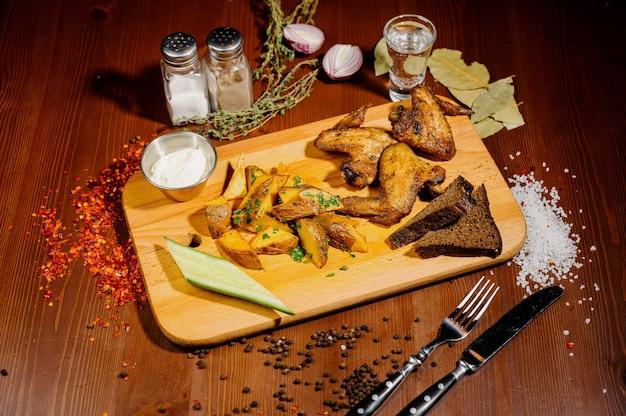 Gegrillte hühnerflügel des grillens schließen oben mit pommes frites, soße auf hölzernem hintergrund. fleisch-lebensmittel-konzept. draufsicht