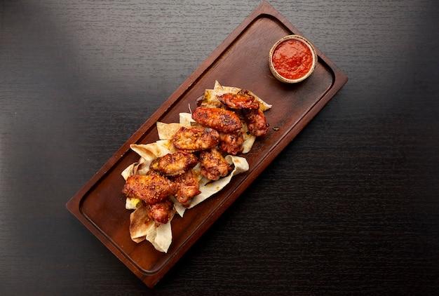 Gegrillte hühnerflügel in soße, mit ketchup, auf einem holzbrett, auf einem dunklen hintergrund