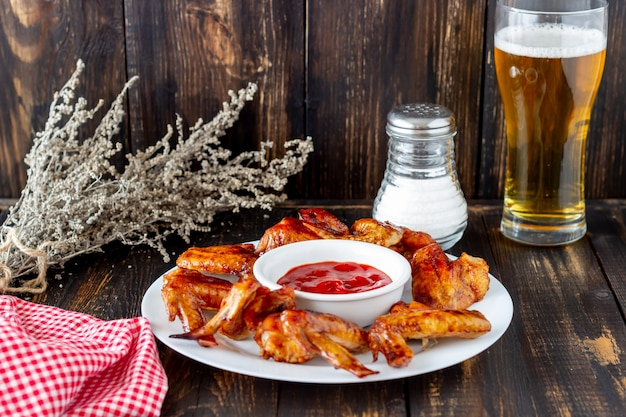 Gegrillte hühnerflügel mit bier und roter soße auf einem hölzernen hintergrund. snack zum bier. grill. rezepte.